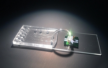 The hybrid device integrates a microfluidic chip for sample preparation and an opto-fluidic chip for optical detection of individual molecules of viral RNA (photo: Joshua Parks)
