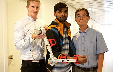 Simon Christensen (left), Muhammad Raza Ul Islam and Shaoping Bai (right) with the first model of a portable robotic arm (photo: Jakob Brodersen)