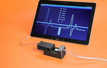A device developed at EPFL is capable of monitoring in real-time five vital substances for patients in ICU, along with a preview of the tablet app designed to monitor the values (photo: Alain Herzog/EPFL)