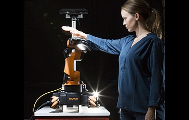Researcher Marianne Bakken attempting to get close and personal with a robot arm – moving in all directions to try to get the robot to collide with her; but it manages to avoid her every time (photo: Werner Juvik/SINTEF)