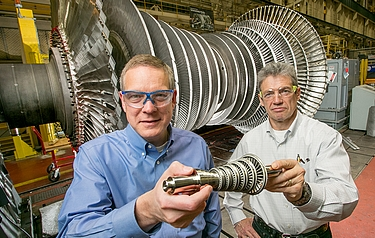 Doug Hofer and Vitali Lissianski holding the 3D printed mini-turbine in front of an actual size power generation steam turbine (photo courtesy of Business Wire)