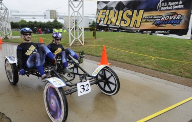 The Greenfield Central High School Rover Team from Greenfield, Indiana, crosses the finish line during the 2015 Human Exploration Rover Challenge. (Credits: NASA/MSFC/Emmett Given)