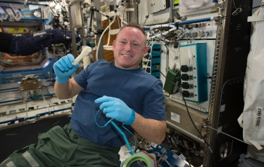 Astronaut holding up a 3D printed tool in the ISS. Image courtesy of NASA