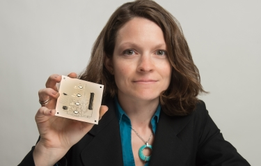 Goddard technologist Beth Paquette holds a 3in by 3in ceramic board with four radiation-hardened digital-to-analogue converter chips. (Credits: NASA/W. Hrybyk)