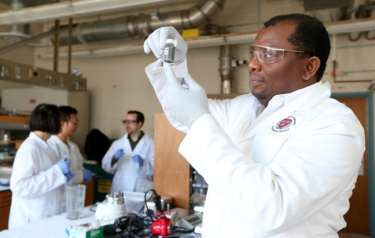 Martin Thuo holds a vial of the liquid-metal particles produced by his research group. Working behind him are, left to right, Simge Cinar, Jiahao Chen and Ian Tevis. (Photo by Christopher Gannon)