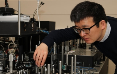 Bristol PhD student Xiaogang Qiang and the primitive photonic quantum processor he designed with UWA researchers to simulate quantum walks. Image credit: Gerardo Villarreal Garcia. © University of Bristol