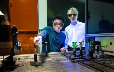 Adrian Sabau and Jian Chen work with a laser to prepare the surface of carbon fibre composites and aluminium to create superior bonds that can absorb 200 percent more energy than conventional bonds. (Credit: Oak Ridge National Lab)
