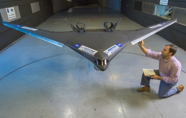 Boeing engineer Stephen Provost checks out a blended wing body model before a wind tunnel test run at NASA Langley. (Credits: NASA/David C. Bowman)