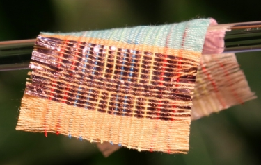 A piece of fabric woven with special strands of material that harvest electricity from the sun and motion. (Credit: Georgia Tech)