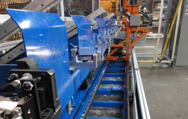 End view of the custom drilling machine. The orange frame is the transversing drillhead driven by the Nexen Roller Pinion System at base of machine. Notice the level of aluminium debris on the floor of the machine. (Photo credit: Lumco Manufacturing)