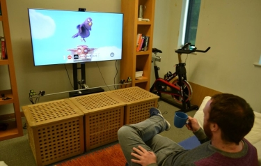 Lancaster University researcher Christopher Clarke selects a channel to watch by using his mug as a remote control. He moves his drink left or right until finding the station he wants to watch. (Credit: Lancaster University)