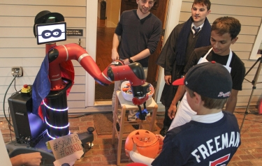 Wearing a mask, cape and hat, Sawyer the robot gives out candy on Halloween. (Credit: Georgia Tech)