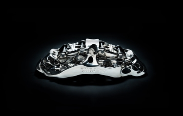 This brake caliper is the largest titanium functional component produced by 3D printing in the world – developed by Bugatti. The photo shows the caliper together with pistons and pads. (Credit: 2018 Bugatti Automobiles S.A.S.)