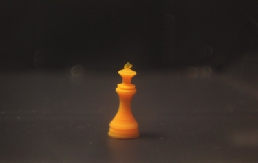 A tiny chess king, 3D-printed with a temperature-responsive hydrogel, in cold water. It contains 73 percent water but remains solid. (Credit: Daehoon Han/Rutgers University-New Brunswick)