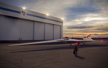 An artist's concept of the low-boom flight demonstrator outside the Lockheed Martin Aeronautics Company's Skunk Works hangar in Palmdale, California. (Credits: Lockheed Martin)