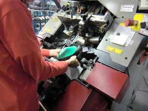 An operator cuts the overabundant leather on the last with a semi-automatic machine