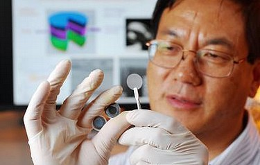 Georgia Tech researcher Zhong Lin Wang holds the components of a new self-charging power cell that uses piezoelectric materials to directly convert mechanical energy to chemical energy