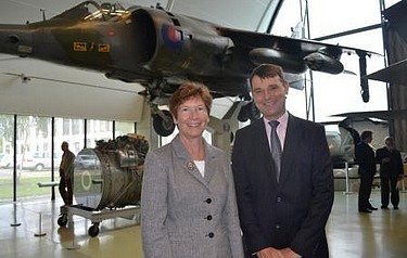 Professor Isobel Pollock and Air Vice-Marshall Peter Dye stand in front of  the Harrier Jump Jet at the RAF Museum, Hendon