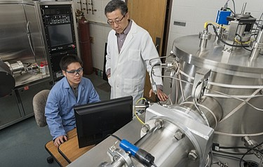 Professor John Xiao (standing) and research associate Xin Fan work with the high vacuum magnetron deposition system, which is used to fabricate layered thin films in a vacuum for spintronics research