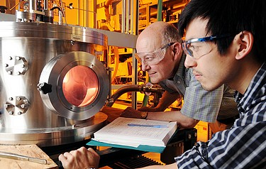 Georgia Tech professor Dennis Hess and graduate research assistant Lester Li observe oxygen plasma treatment that exposes the cellulose nanofibrils on their superamphiphobic paper samples